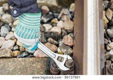 Man's hand with Adjustable wrench near the railway track