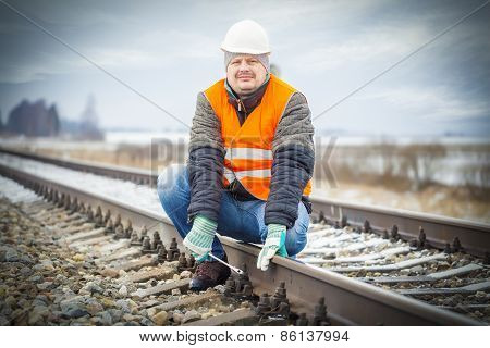 Worker with adjustable wrench on the railroad