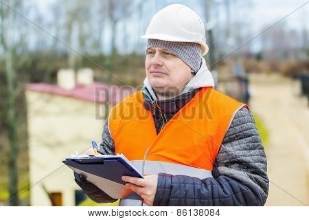 Construction employee with documentation near building