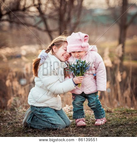 little girl and her sister holding a bouquet of snowdrops