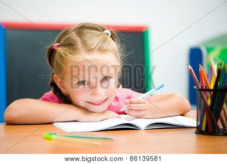 beautiful little girl at the desk with a pen