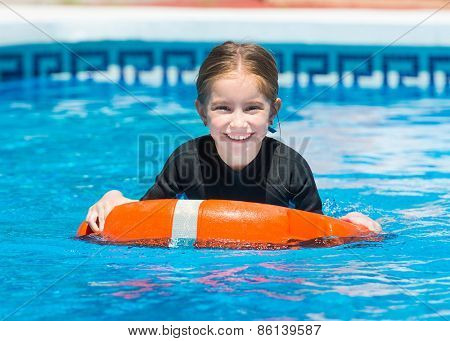happy little girl swims in a wetsuit with a lifeline in the pool in  summer
