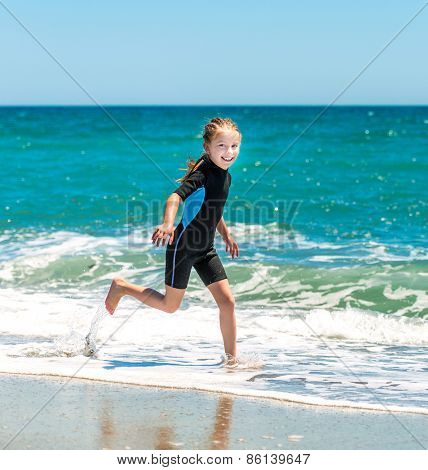 laughing  little girl runing in a wetsuit on the seashore