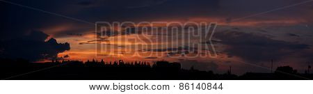 sunset panorama over the city with red shades and clouds