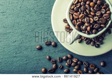 Coffee cup full of roasted coffee beans.