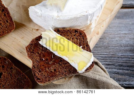 Camembert Cheese, Rye Bread Slices And Honey On A Board