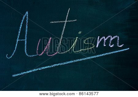 the word autism with its letters written with chalk of different colors on a green chalkboard
