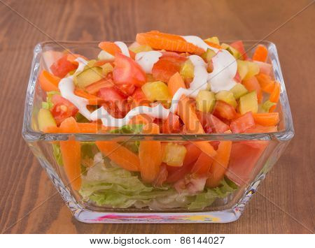 Appetizer salad with lettuce, tomato, carrots and pickles topped with dressing, on dark wooden table