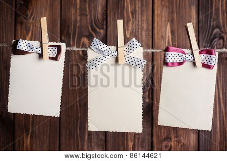 Three Old Paper Sheets With Bows Hanging On Clothesline Against Wooden Background