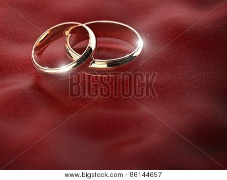 pair of golden wedding rings on red leather