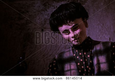 Close Up of Male Mannequin with Dark Hair Dressed in Polka Dot Shirt and Plaid Vest in Purple Light