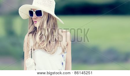 Summer Fashion Romantic Lady In The Park On A Walk. Fashion Hat And Sunglasses