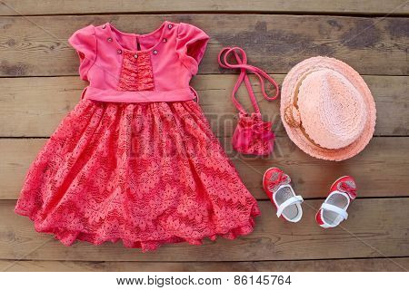Summer children's clothing: dress, purse, hat, shoes on wooden background