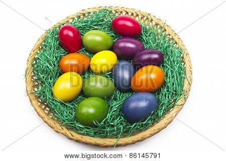 Colorful Easter eggs in a basket on the grass