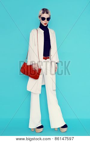 Fashion Lady In Stylish White Clothes. White Trousers And A Raincoat On Blue Background