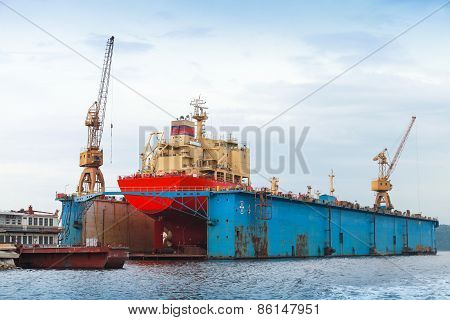Floating Blue Dry Dock With Red Tanker Under Repair