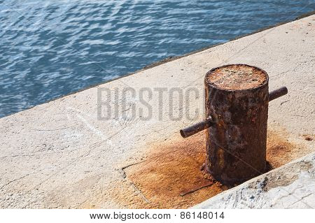 Old Rusted Mooring Bollard On Concrete Pier