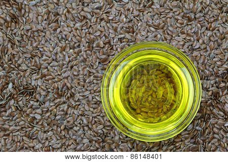 A bowl of cold pressed Linseed yellow oil on flaxseed background. flaxseed are seeds from flax plant