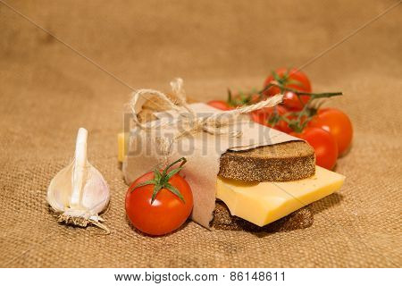 Sandwich With Cheese Wrapped In Paper, Cherry Tomatoes And Garlic On Old Cloth