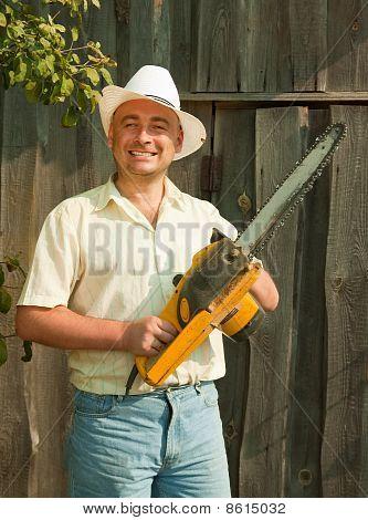 Trabajador con motosierra contra la pared de madera