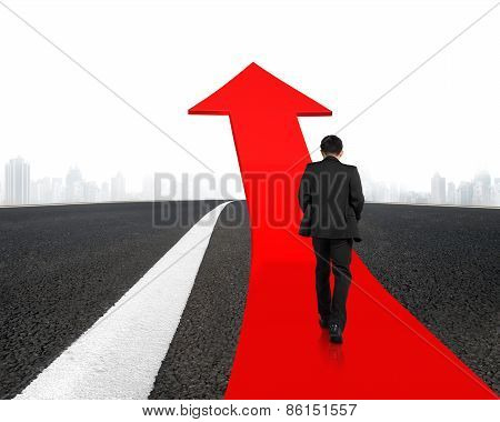 Businessman Walking On Arrow Road With Asphalt Pavement And Cityscape