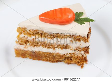 Slice of homemade tasty carrot sponge cake with pastry cream and little orange carrots