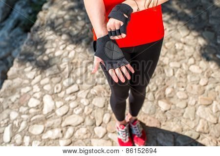 Sport woman putting on gloves