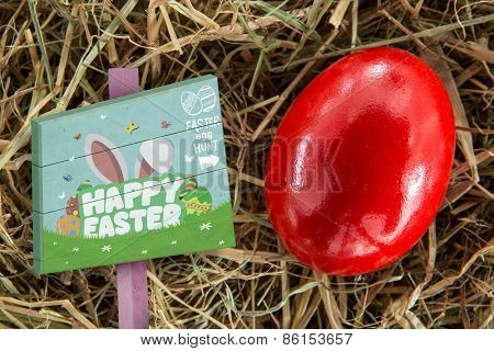Easter egg hunt sign against red egg on straw