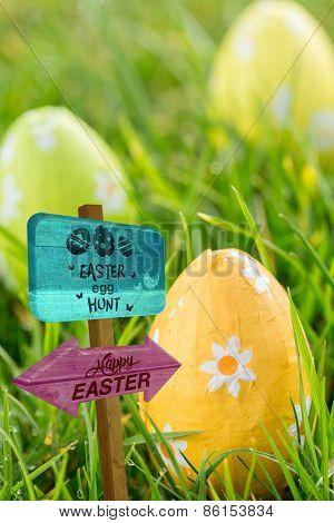 Easter egg hunt sign against easter eggs in the grass