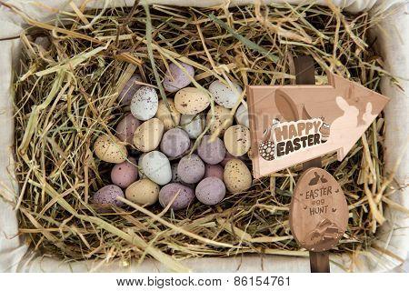 Easter egg hunt sign against little candy easter eggs in a basket