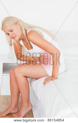 Portrait of a blonde woman having a stomachache in her bedroom