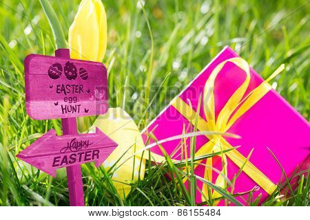 Easter egg hunt sign against pink gift box with easter egg and yellow tulip