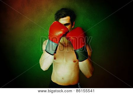 Muscly man wearing red boxing gloves in guard position against dark background