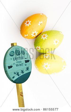 Easter egg hunt sign against overhead of three easter eggs
