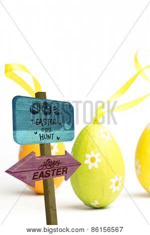Easter egg hunt sign against three easter eggs