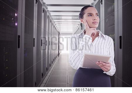 Confused businesswoman using a tablet pc against data center
