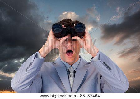 Suprised businessman looking through binoculars against blue and orange sky with clouds