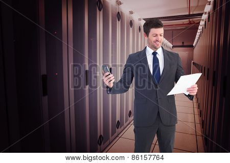 Businessman sending text holding page against data center
