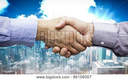 Hand shake in front of wires against city skyline