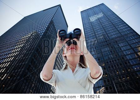 Businesswoman looking through binoculars against low angle view of skyscrapers