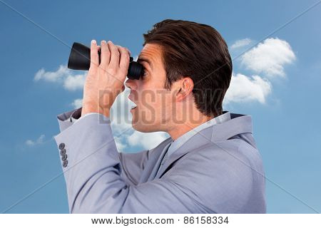 Visionary businessman looking to the future against cloudy sky
