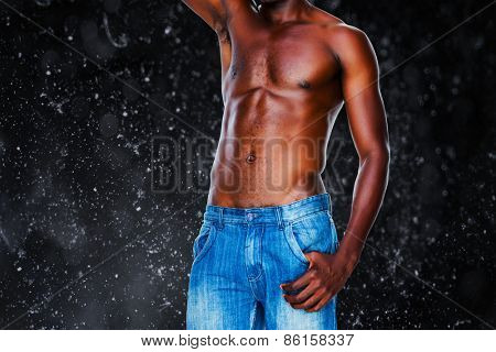 Mid section of a shirtless muscular man against black background