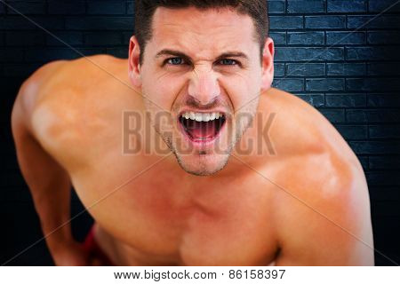 Bodybuilder shouting against black background