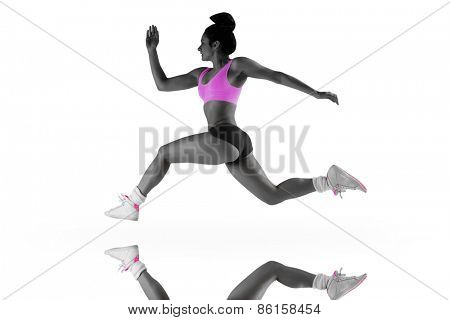Fit brunette running and jumping against mirror