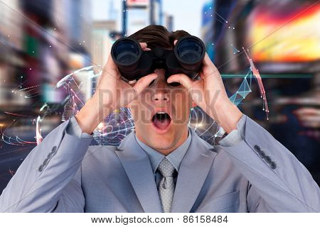 Suprised businessman looking through binoculars against global technology background in blue