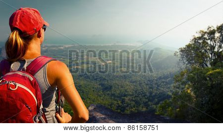 Young lady hiker with backpack standing on top of the mountain and enjoying valley view