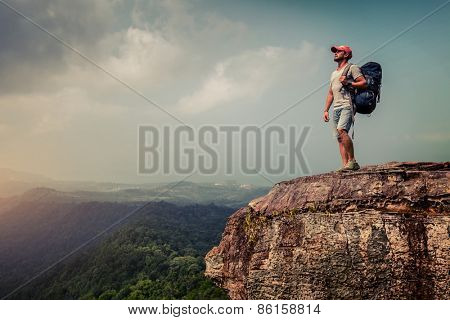 Young hiker with backpack standing on top of the mountain