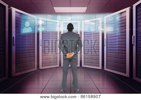 Young businessman standing with hands behind back against application interface