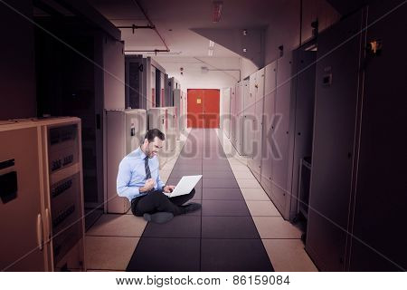 Cheering businessman sitting using his laptop against data center