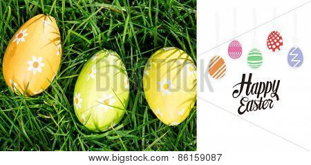 happy easter graphic against three easter eggs nestled in the grass